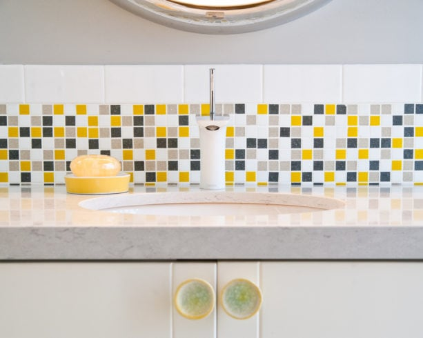 fresh look with grey, white, and yellow mosaic tile for the backsplash