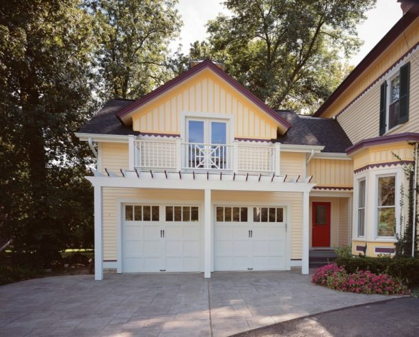 mid-sized ornate carport in front of painted white garage's door