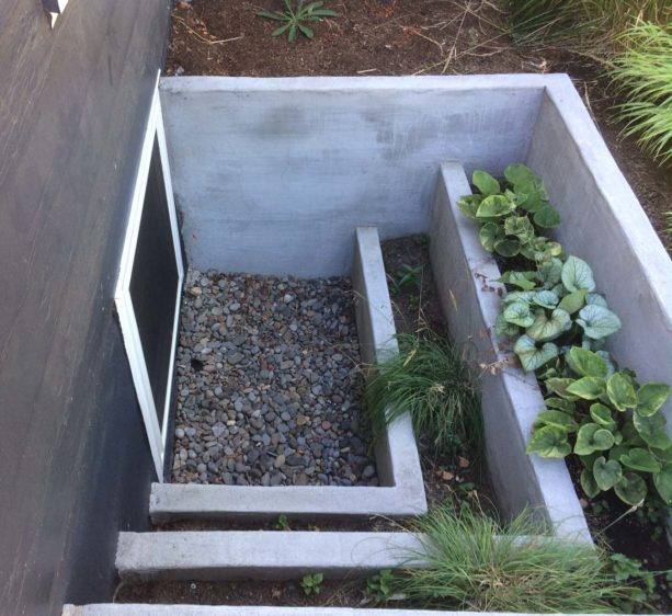 poured concrete basement window well with tiered planter boxes