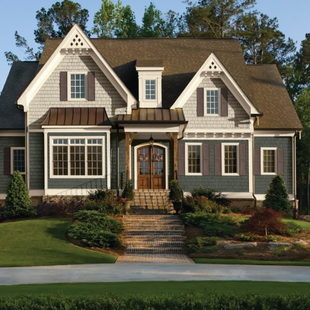 a traditional two-toned grey house with brown roof