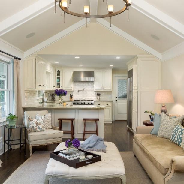 crisp white small peninsula kitchen and classic living room combo