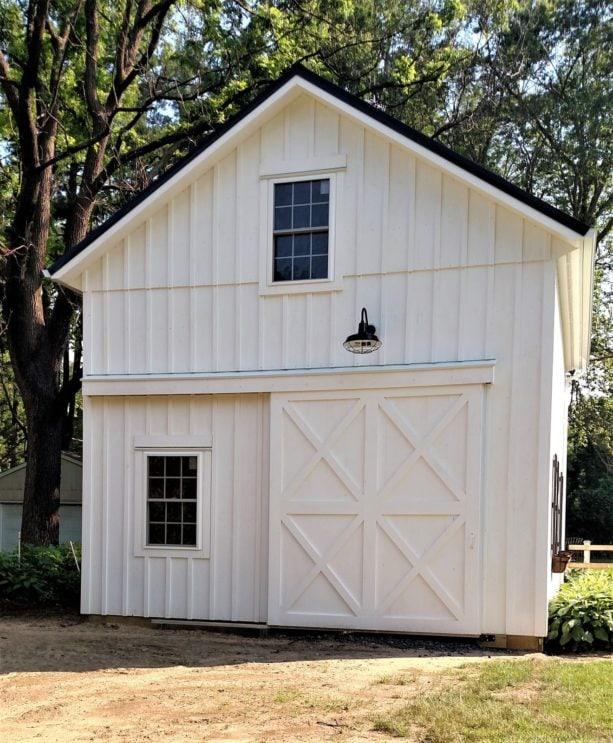 white side sliding garage door completed under goose neck lighting