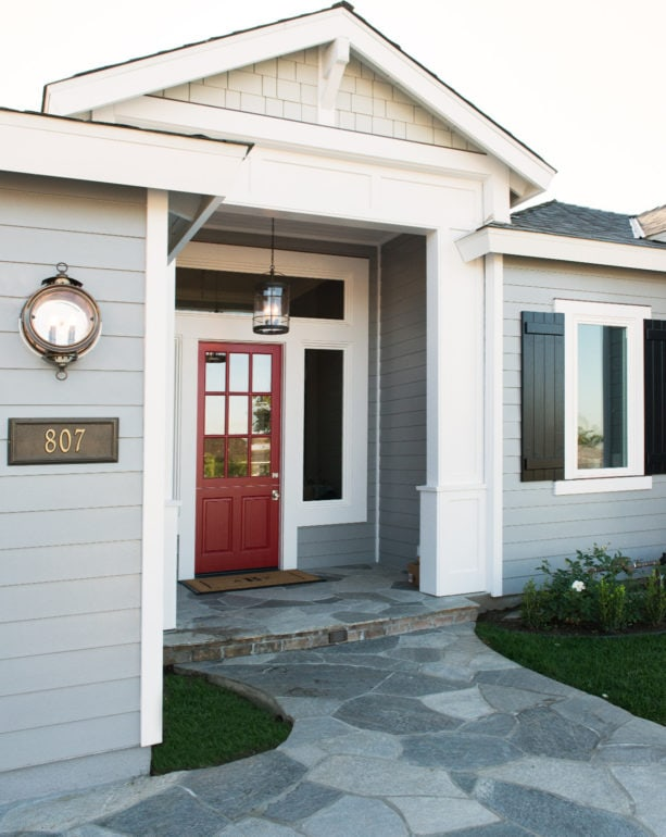 berry-red front door in a light grey exterior with white trim