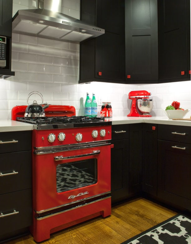a red kitchen range with black grate and chrome accents