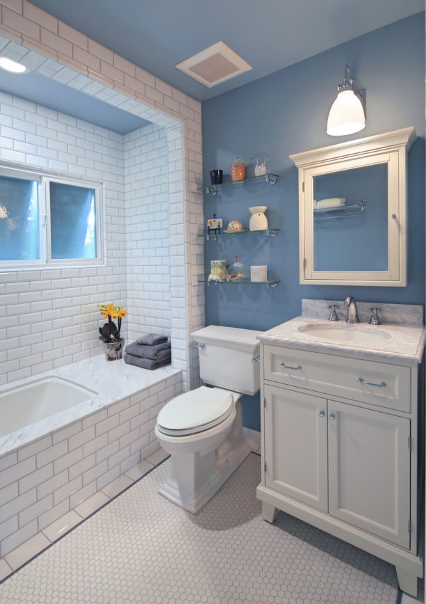 a small bathroom with white tiles and blue walls to create a cozy feeling
