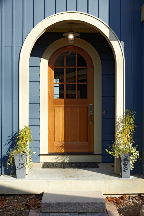 a traditional wooden arched front door with simple trim