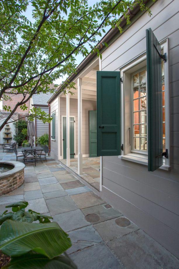 a tan wood siding with greyish green shutters