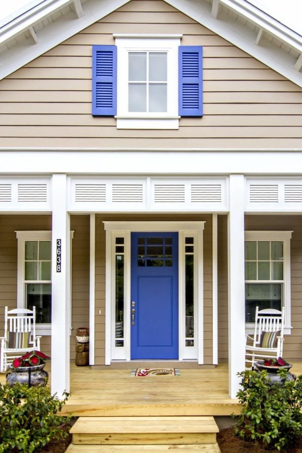 a tan beach-style house with blue shutters