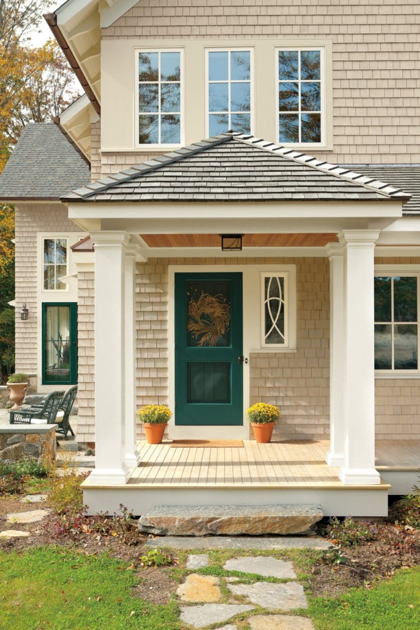 a traditional front door trim united with the window trim next to it