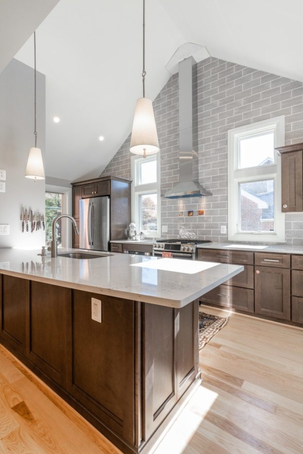 grey subway tile backsplash kitchen color mixes nicely with brown recessed-panel cabinets for a more open look