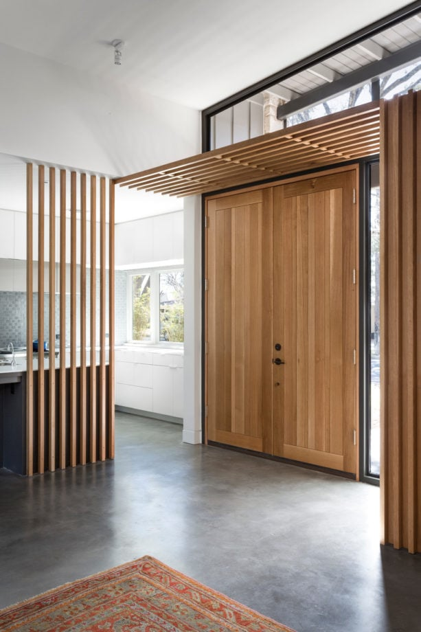 concrete floor entryway with tiny vertical wood slat wall