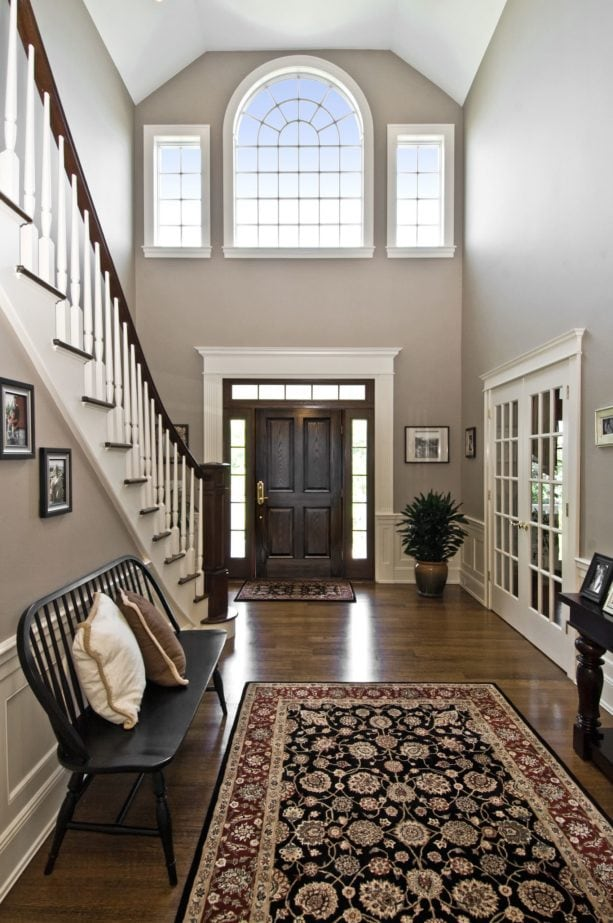 a historical feel in a traditional entry with dark-stained walnut floor and white trim
