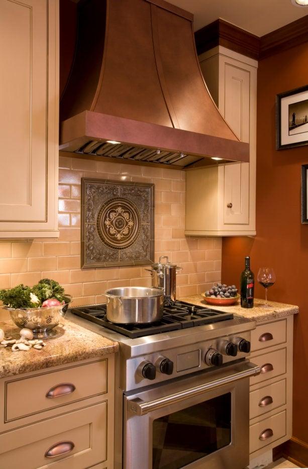 english tudor kitchen with antique medallion backsplash behind stove only