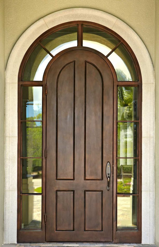 a traditional entry solid wood door with transom surround by Sun Coast Iron Doors