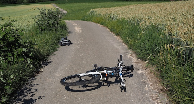 Bike lying on a dirt road several metres from a backpack after an apparent wipeout