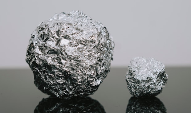 Two balls of crumpled aluminum foil, one large, one small