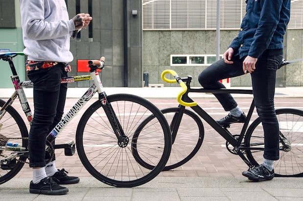 Two cyclists, including one on a fixie, chat before getting ready to ride