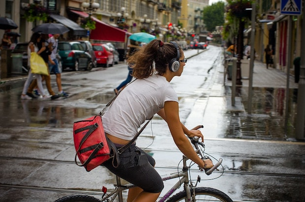 Cyclist with headphones covering her entire ear