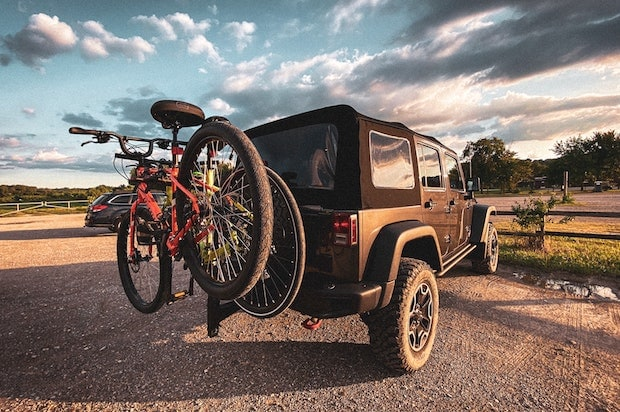 Two bikes loaded on the rear rack of a Jeep Wrangler