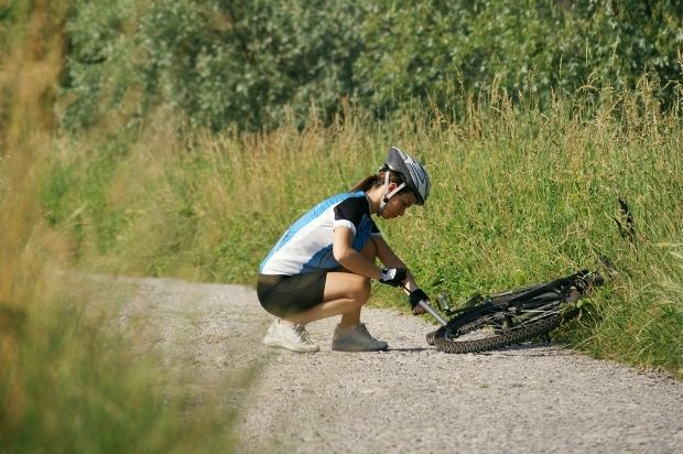 Cyclist paused on a gravel trail to pump up a soft tire