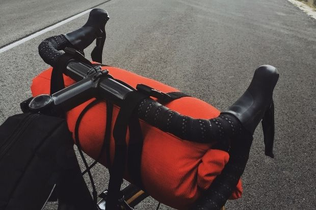 sleeping bag packed on the front of a bike with drop handlebars