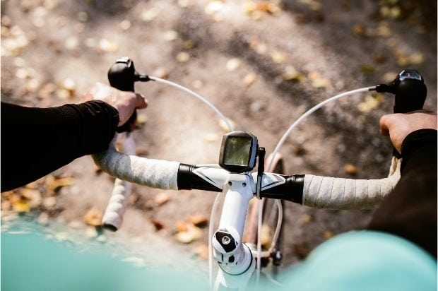 A cyclist's view of his own hands on drop handlebars