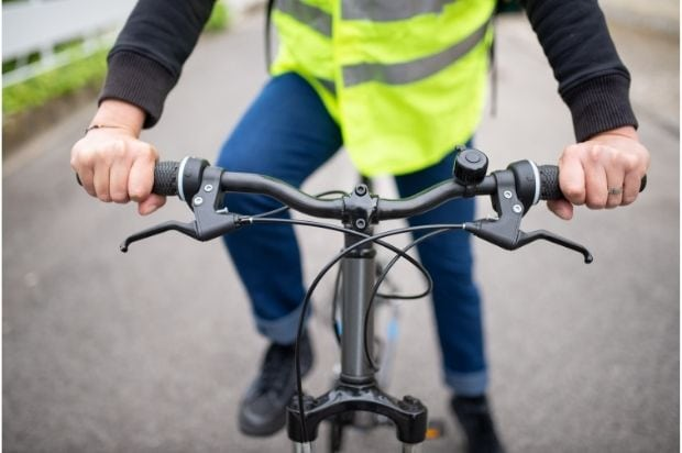 A cyclist with his hands on flat handlebars