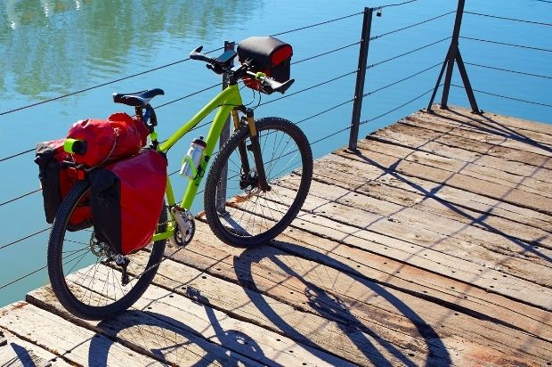 Touring bike with panniers parked on a waterfront wharf