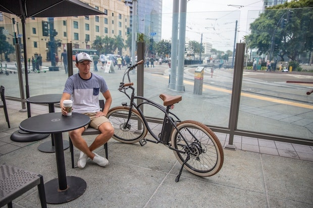 Man sitting at a coffee shop drinking coffee next to his bike