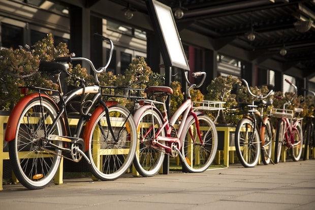 Five cruiser bikes parked against a rail