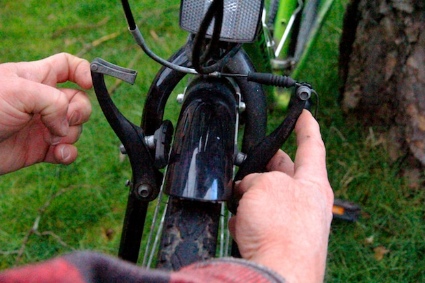 A pair of hands releasing a V-brake from the front wheel of a bike
