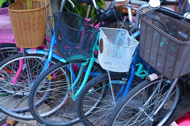 A row fo bikes with colorful baskets