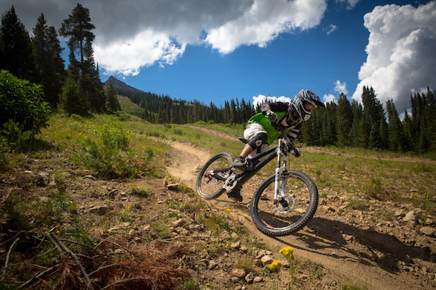 Mountain biker barreling down a mountain trail with blue sky behind