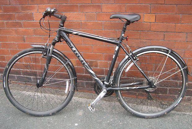 Trek hybrid bike against a brick wall