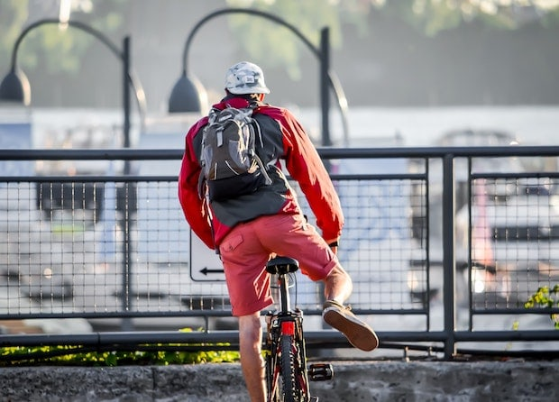 Man dismounting his bicycle, viewed from behind