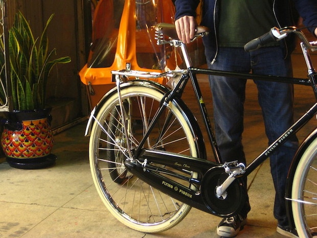 Man holding a cruiser bike in a bike shop