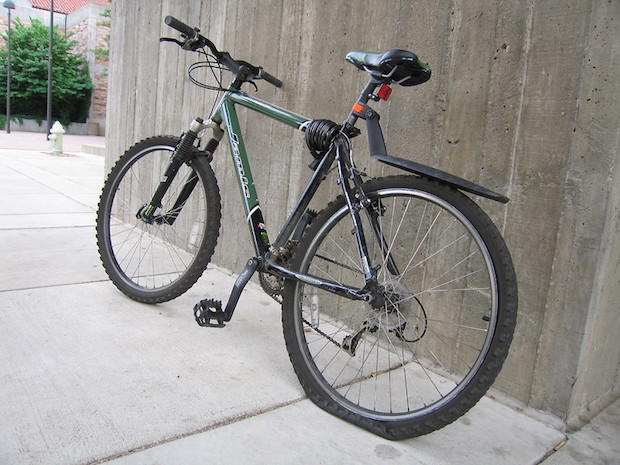 A mountain bike with a flat rear tire leaning against a concrete wall
