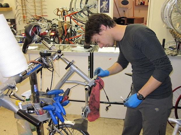 Mechanic in a bike shop cleaning a folding bike