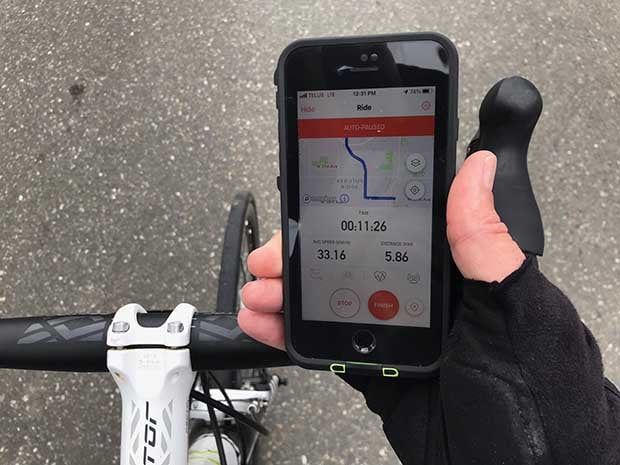 Closeup of a cyclist holding an iPhone above the handlebars with the Strava app running
