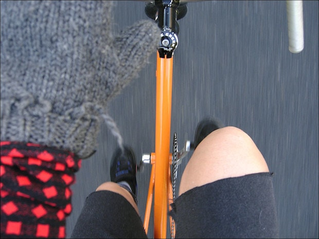 A cyclist's view looking down at her own knees while riding