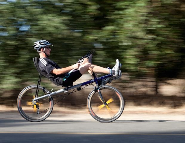 Side view of a man cycling on a recumbent bike