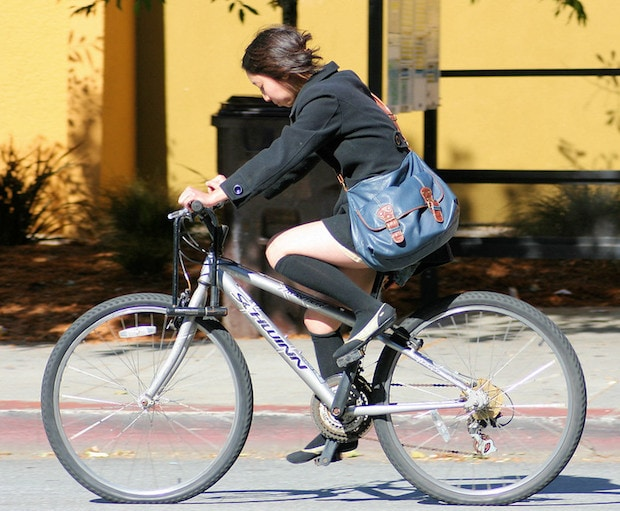 Side view of a woman riding a bike with her upper knee bent at an extreme angle