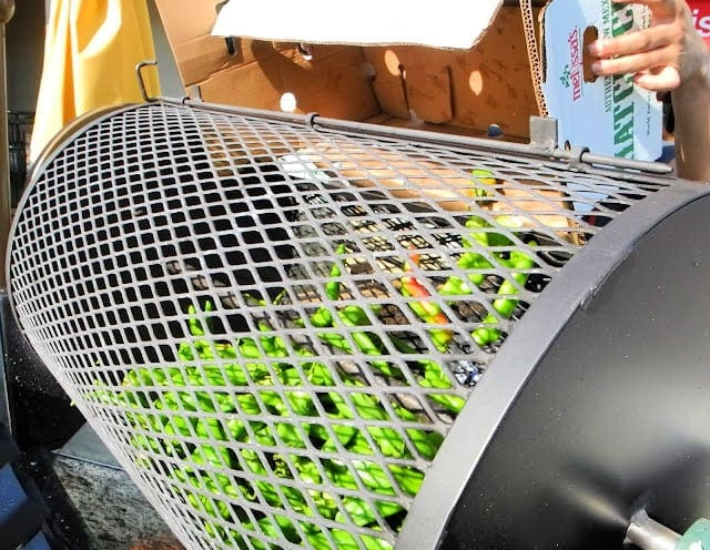 roller cage filled with green chiles and more from a produce carton labeled Melissa's Produce being dumped inside