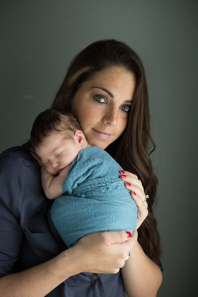 mom looking at camera holding baby wrapped in teal during newborn portrait session