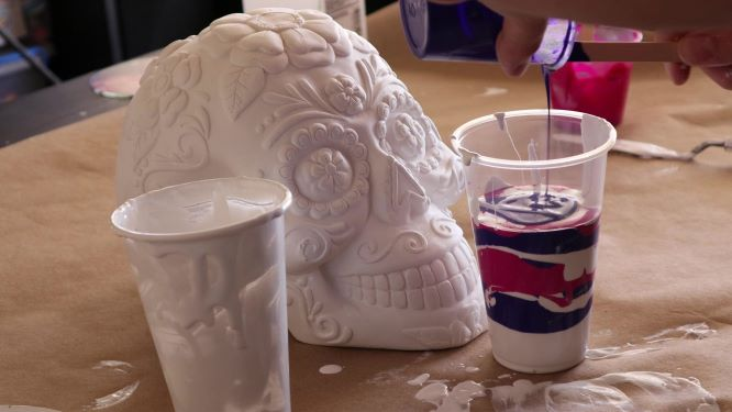 sugar skull art in progress, pouring paint on top of