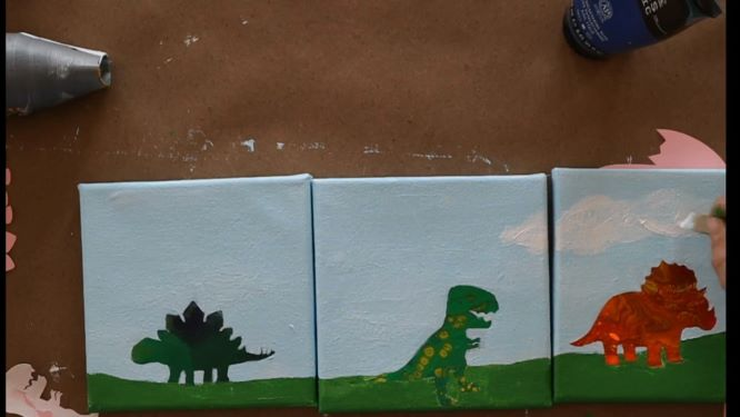 painting the clouds in the background in of the dinosaur painting