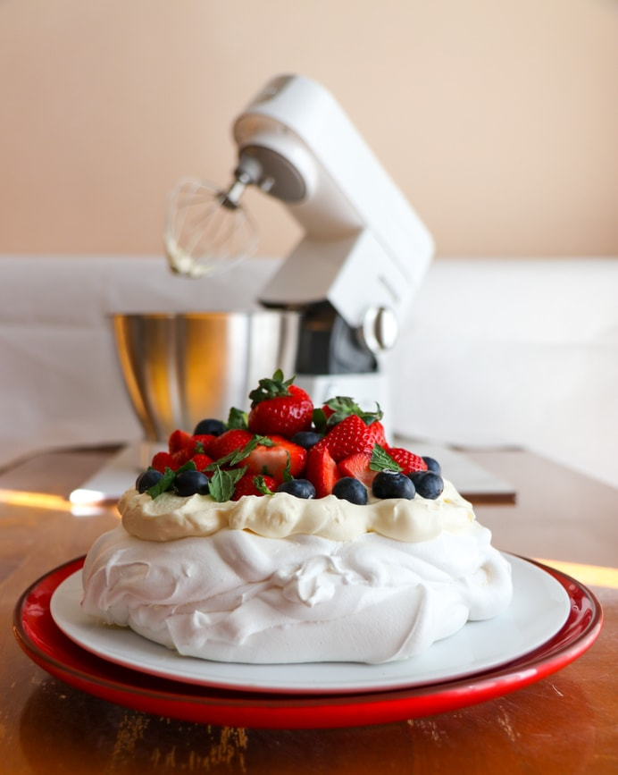 Pavlova recipe with whipped cream, strawberries and raspberry coulis in front of a Kenwood Chef stand mixer.