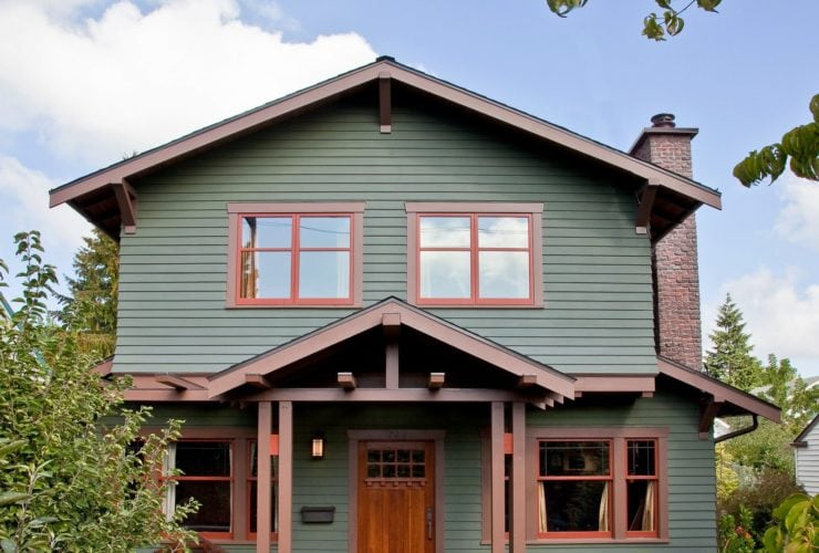 lovely moss green house with wooden nutmeg brown trim