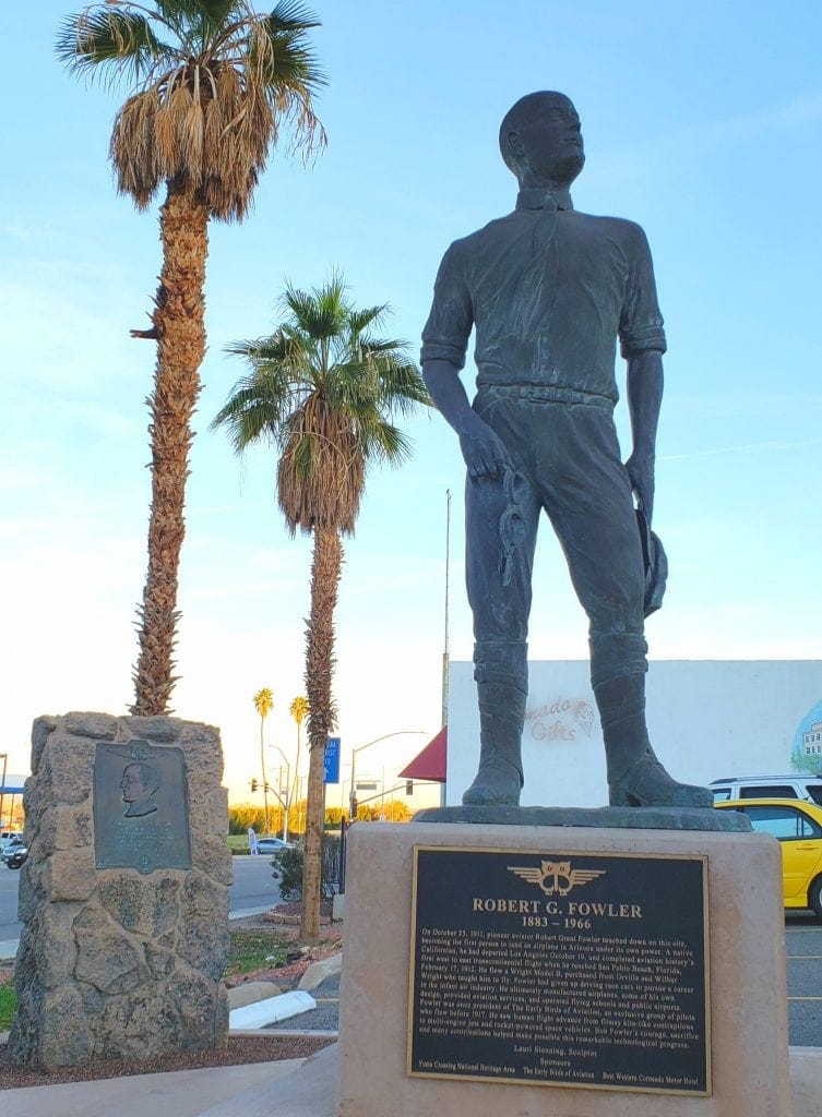 Statue of early airplane pilot holding leather googles against palm trees and cloudless sky.
