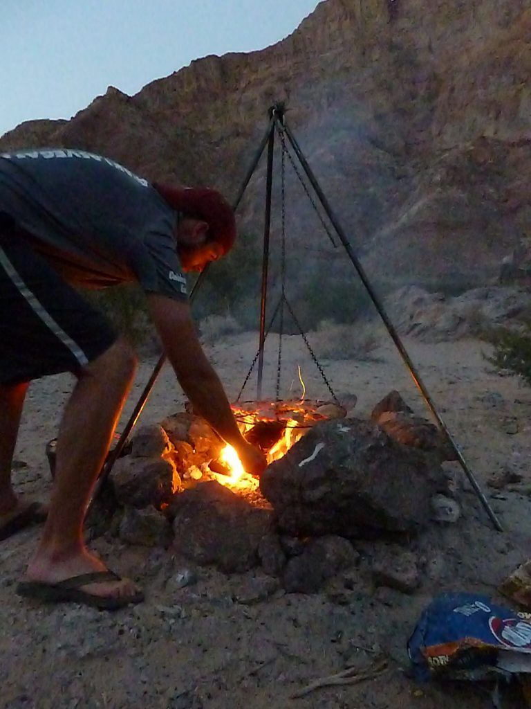 As night falls, Gary stirs the campfire on our Kayak Hoover Dam Black Canyon adventure.